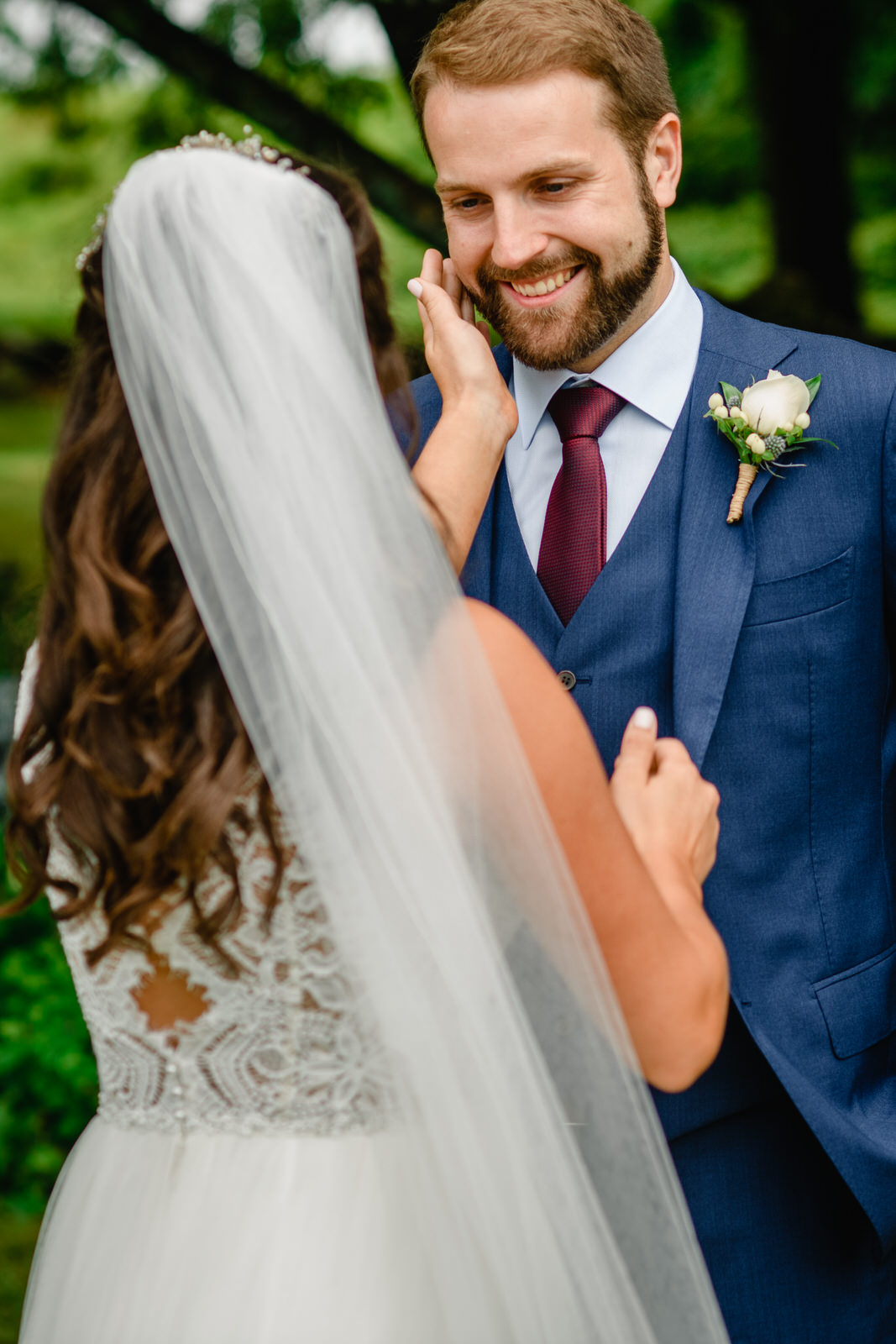 bride touching grooms face in first look emotional moment